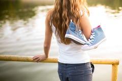 Pares atados de zapatillas de deporte que cuelgan en una muchacha Imágenes de archivo libres de regalías
