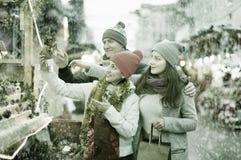 Pares atentos de la familia con la muchacha adolescente que elige decoros de la Navidad Foto de archivo libre de regalías