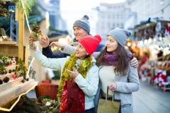 Pares atentos de la familia con la muchacha adolescente que elige decoros de la Navidad Fotos de archivo