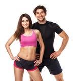 Pares atléticos - o homem e a mulher após a aptidão exercitam no branco imagens de stock