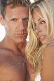 Pares atractivos atractivos del hombre y de la mujer en la playa Foto de archivo