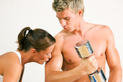 Pares atractivos con pesas de gimnasia en gimnasia Imagenes de archivo