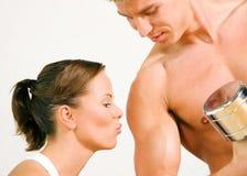 Pares atractivos con pesas de gimnasia en gimnasia Foto de archivo