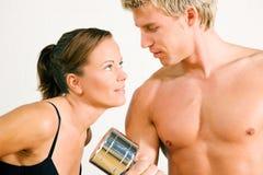 Pares atractivos con pesas de gimnasia en gimnasia Fotografía de archivo libre de regalías
