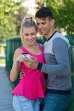 Pares atractivos con smartphone afuera Fotos de archivo
