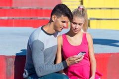 Pares atractivos con smartphone afuera Imagen de archivo