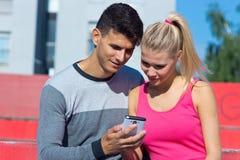 Pares atractivos con smartphone afuera Fotografía de archivo libre de regalías