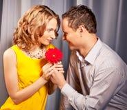 Pares atractivos de amantes. El hombre presenta la flor. Imagenes de archivo