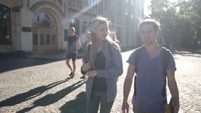 Pares atractivos de los estudiantes que caminan en campus almacen de metraje de vídeo