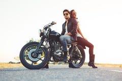 Pares atractivos de motoristas en la motocicleta de la aduana del vintage Imágenes de archivo libres de regalías