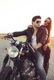 Pares atractivos de motoristas en la motocicleta de la aduana del vintage Foto de archivo libre de regalías