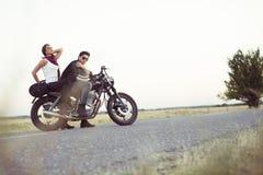 Pares atractivos de motoristas en la motocicleta de la aduana del vintage Fotos de archivo libres de regalías