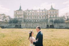 Pares atractivos del recién casado que abrazan en el césped soleado verde cerca de palacio barroco arruinado hermoso Tenencia car Imagenes de archivo