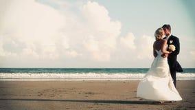 Pares atractivos del recién casado que se besan en la playa en cinemagraph metrajes