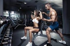 Pares atractivos deportivos jovenes hermosos en gimnasio