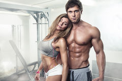 Pares atractivos deportivos jovenes hermosos en gimnasio Imágenes de archivo libres de regalías