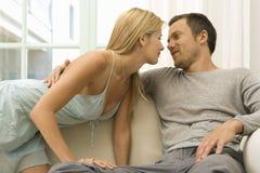 Pares atractivos en el sofá en casa. Imagen de archivo libre de regalías