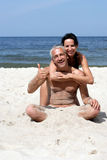 Pares atractivos en la playa Imagen de archivo libre de regalías