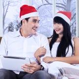 Pares atractivos en sombrero de la Navidad con la tableta Imagenes de archivo