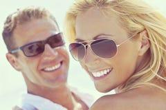Pares atractivos felices de la mujer y del hombre en gafas de sol en la playa imagen de archivo