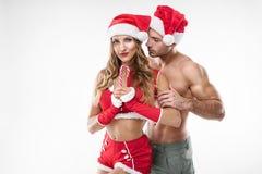 Pares atractivos hermosos en la ropa de Papá Noel imagen de archivo