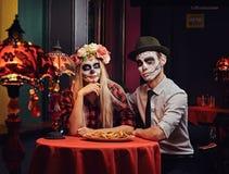 Pares atractivos jovenes con el maquillaje de los undead que come los nachos durante la datación en un restaurante mexicano fotografía de archivo