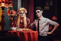 Pares atractivos jovenes con el maquillaje de los undead que come los nachos durante la datación en un restaurante mexicano imagen de archivo