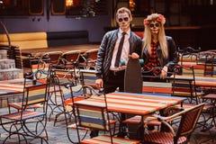 Pares atractivos jovenes con los undead que presentan cerca de restaurante mexicano al aire libre foto de archivo libre de regalías