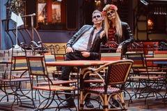 Pares atractivos jovenes con los undead que presentan cerca de restaurante mexicano al aire libre foto de archivo