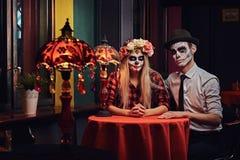 Pares atractivos jovenes con maquillaje de los undead durante la datación en un restaurante mexicano fotos de archivo