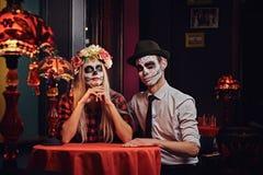 Pares atractivos jovenes con maquillaje de los undead durante la datación en un restaurante mexicano fotos de archivo libres de regalías