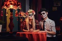 Pares atractivos jovenes con maquillaje de los undead durante la datación en un restaurante mexicano imágenes de archivo libres de regalías