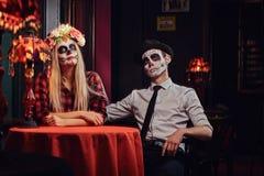 Pares atractivos jovenes con maquillaje de los undead durante la datación en un restaurante mexicano foto de archivo
