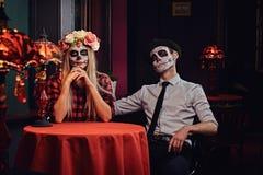 Pares atractivos jovenes con maquillaje de los undead durante la datación en un restaurante mexicano fotografía de archivo