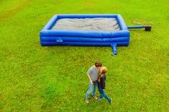 Pares atractivos jovenes en el fondo de un trampolín azul inflable grande en hierba verde fotografía de archivo libre de regalías