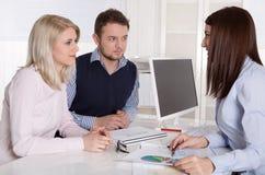 Pares atractivos jovenes en la consulta con el consultor femenino. Imagenes de archivo