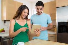 Pares atractivos jovenes felices en casa que miran una tableta elegante que hojea Internet Imagen de archivo libre de regalías