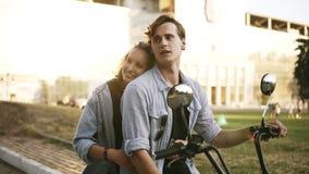 Pares atractivos jovenes que abrazan y que se gozan mientras que se sienta en una bici en la calle Ambas camisas azules que lleva almacen de video