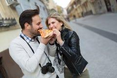 Pares atractivos jovenes que comparten la rebanada de pizza Imagen de archivo libre de regalías