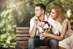 Pares atractivos jovenes que se sientan en banco en el parque y el embraci Imagen de archivo libre de regalías