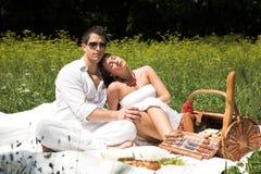 Pares atractivos jovenes que tienen un picknick imagen de archivo libre de regalías