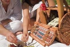 Pares atractivos jovenes que tienen un picknick Fotos de archivo libres de regalías