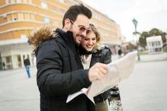 Pares atractivos jovenes sonrientes que miran el mapa Foto de archivo