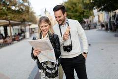 Pares atractivos jovenes sonrientes que miran el mapa Fotos de archivo