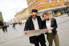Pares atractivos jovenes sonrientes que miran el mapa Imágenes de archivo libres de regalías