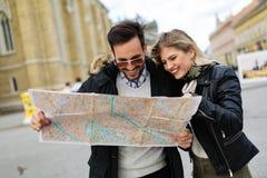 Pares atractivos jovenes sonrientes que miran el mapa Fotografía de archivo