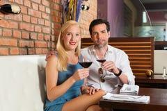Pares atractivos que beben el vino rojo en barra Fotografía de archivo