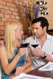 Pares atractivos que beben el vino rojo en restaurante Fotos de archivo