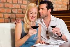 Pares atractivos que beben el vino rojo en restaurante Imagenes de archivo