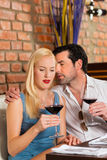 Pares atractivos que beben el vino rojo en restaurante Foto de archivo libre de regalías